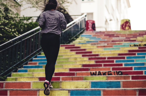Female runner running up coloured steps to get to the street above and carry on her morning run