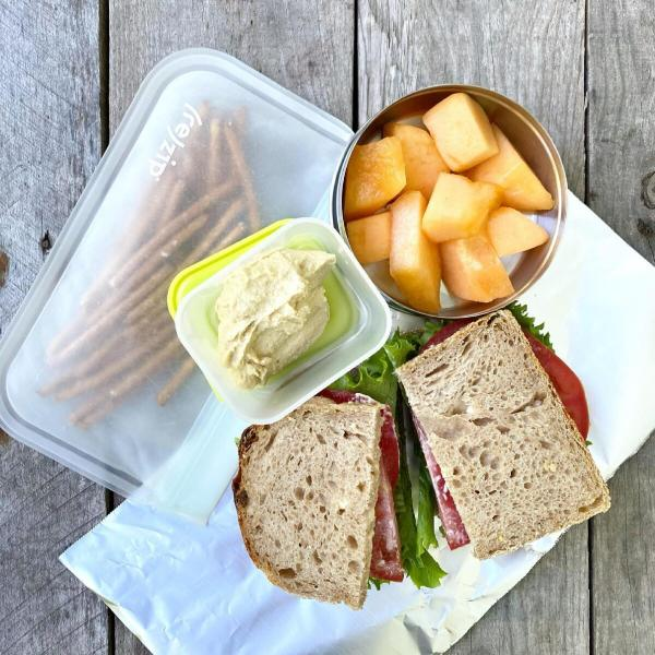 Packed school lunch that includes a BLT sandwich, pretzels with hummus, and cantaloupe.