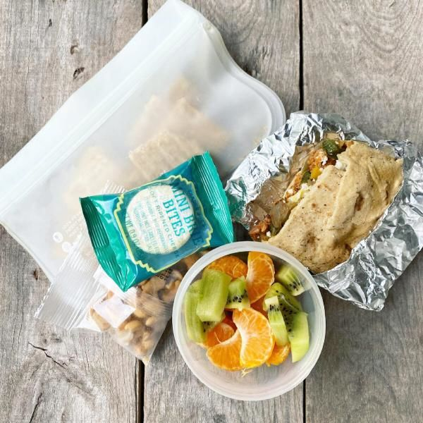 Packed school lunch that includes a Mexican Breakfast Burrito, kiwi and oranges, cashews, and whole-wheat crackers with a mini brie.