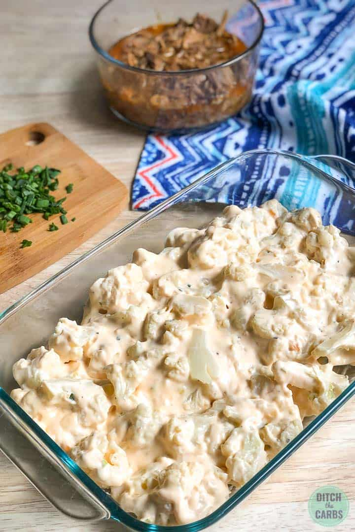 The cauliflower has been tossed in the cheese sauce and then transferred to a clear glass casserole dish.