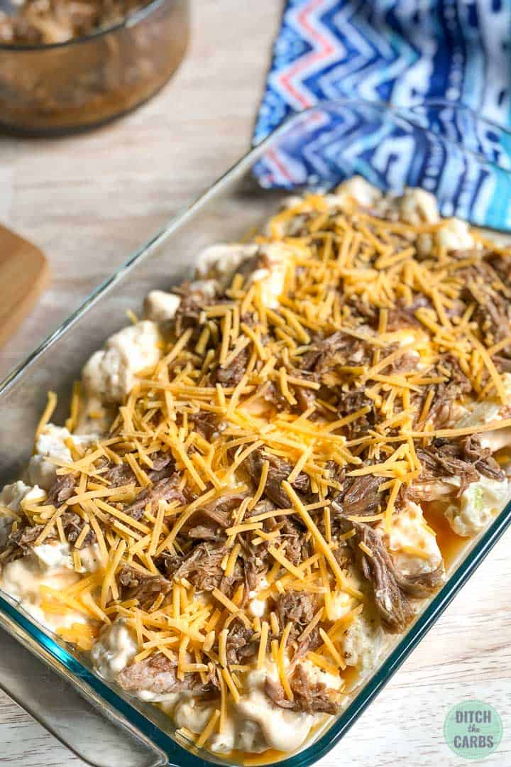 Keto pulled pork mac and cheese assembled in a clear glass casserole dish ready to be baked in the oven.