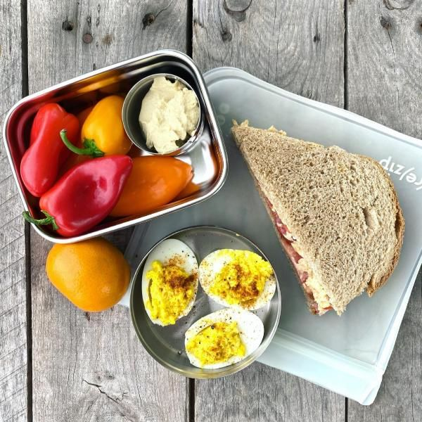 Packed school lunch that includes pimento cheese and tomato sandwich, bell peppers with hummus, an orange, and three deviled eggs.