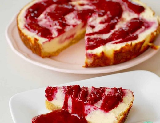 slice of cheesecake with raspberry swirl on a white plate in the foreground and a whole cheesecake in the background