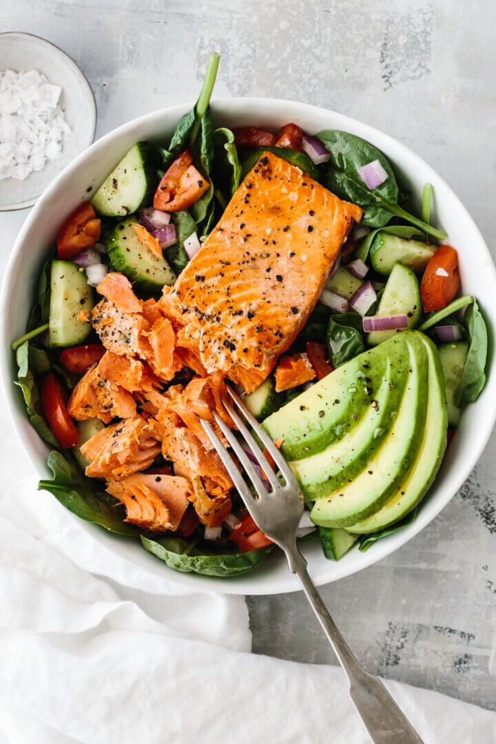 Salmon fillet on salad with avocado slices.