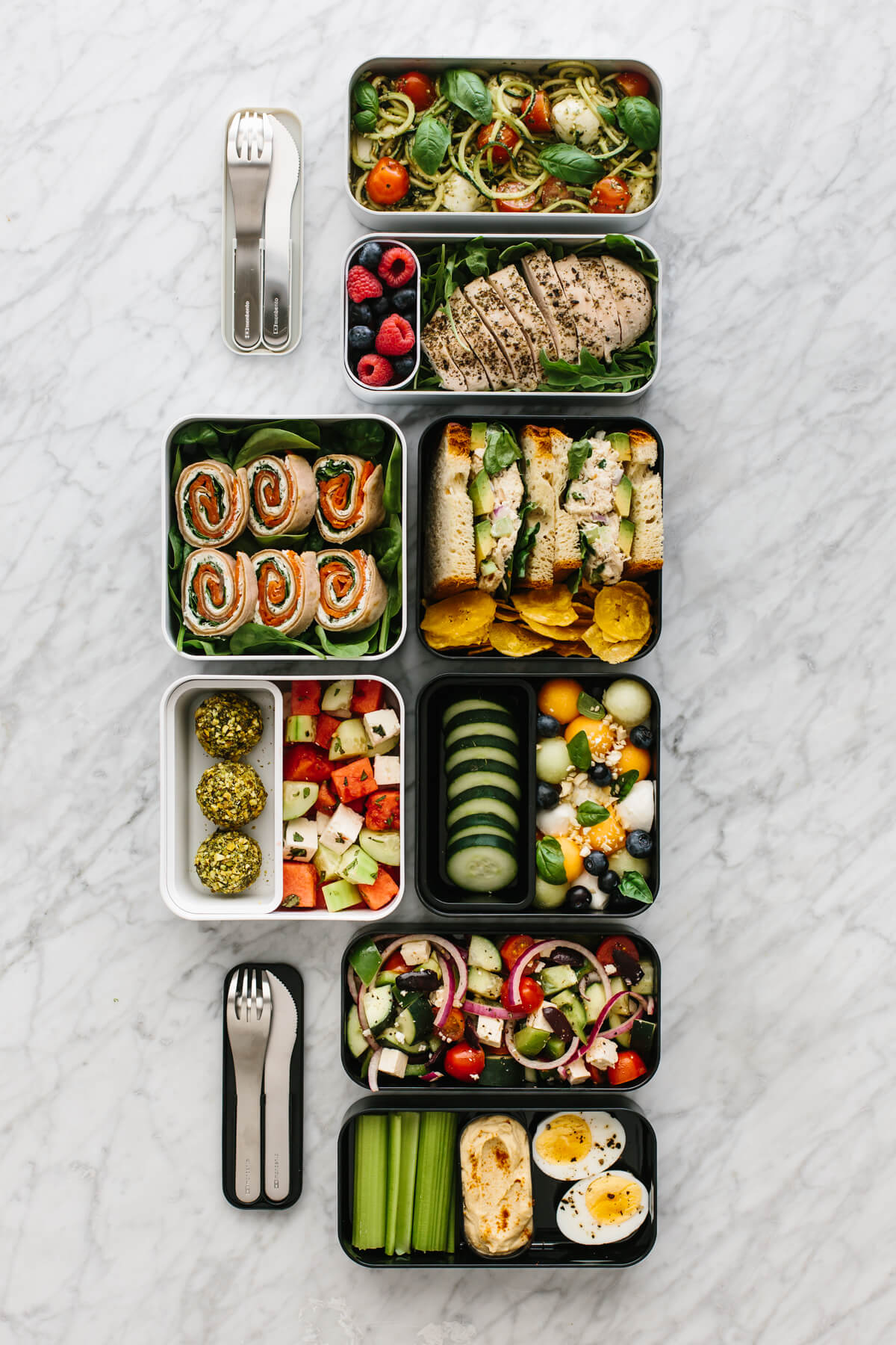 Several bento box lunches arranged next to each other on a countertop.