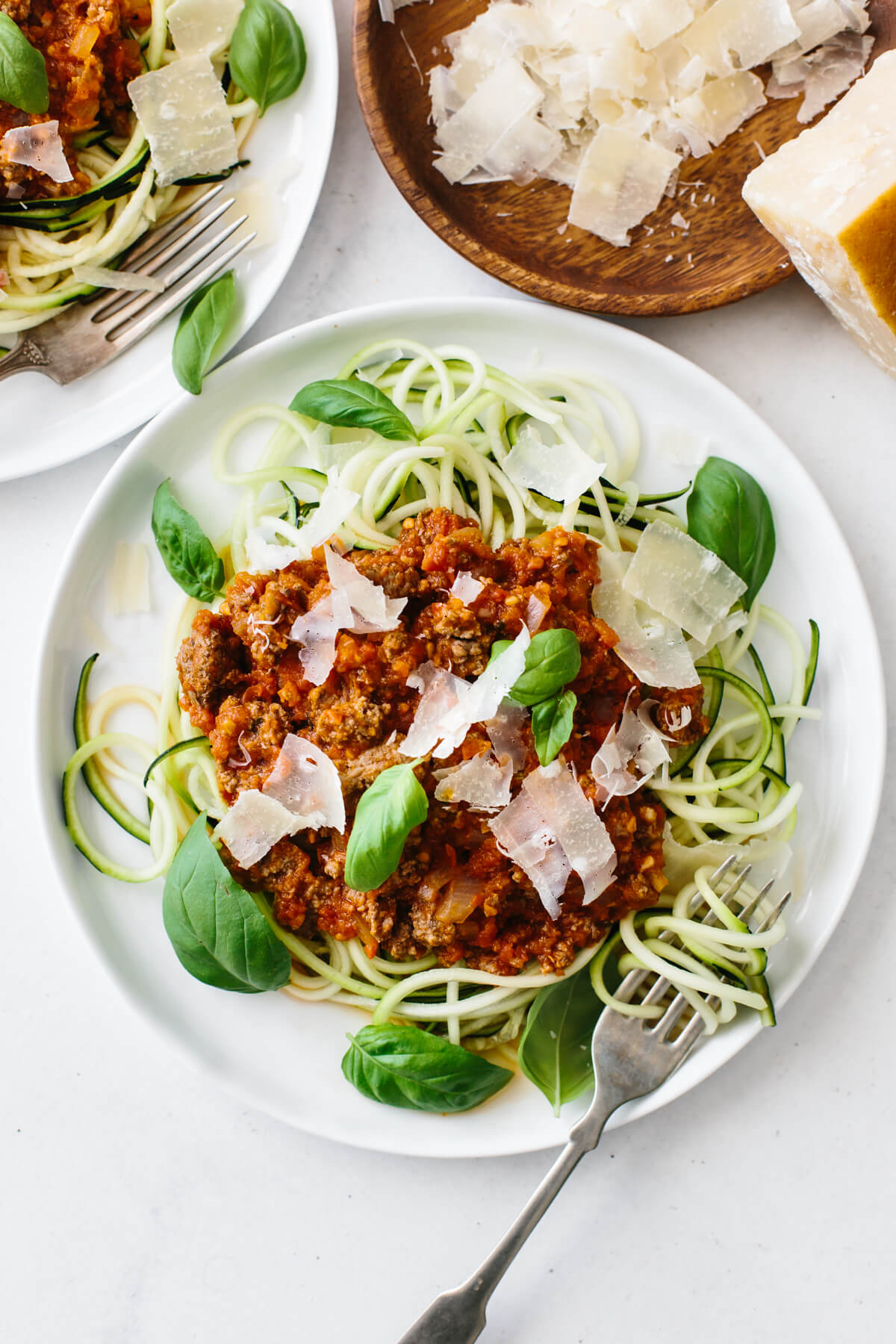 A plate of zucchini noodles topped with bolognese sauce, fresh parmesan and basil.