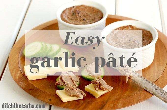 A wooden serving plate with homemade garlic pate, slices of cheese and slices of cucumber