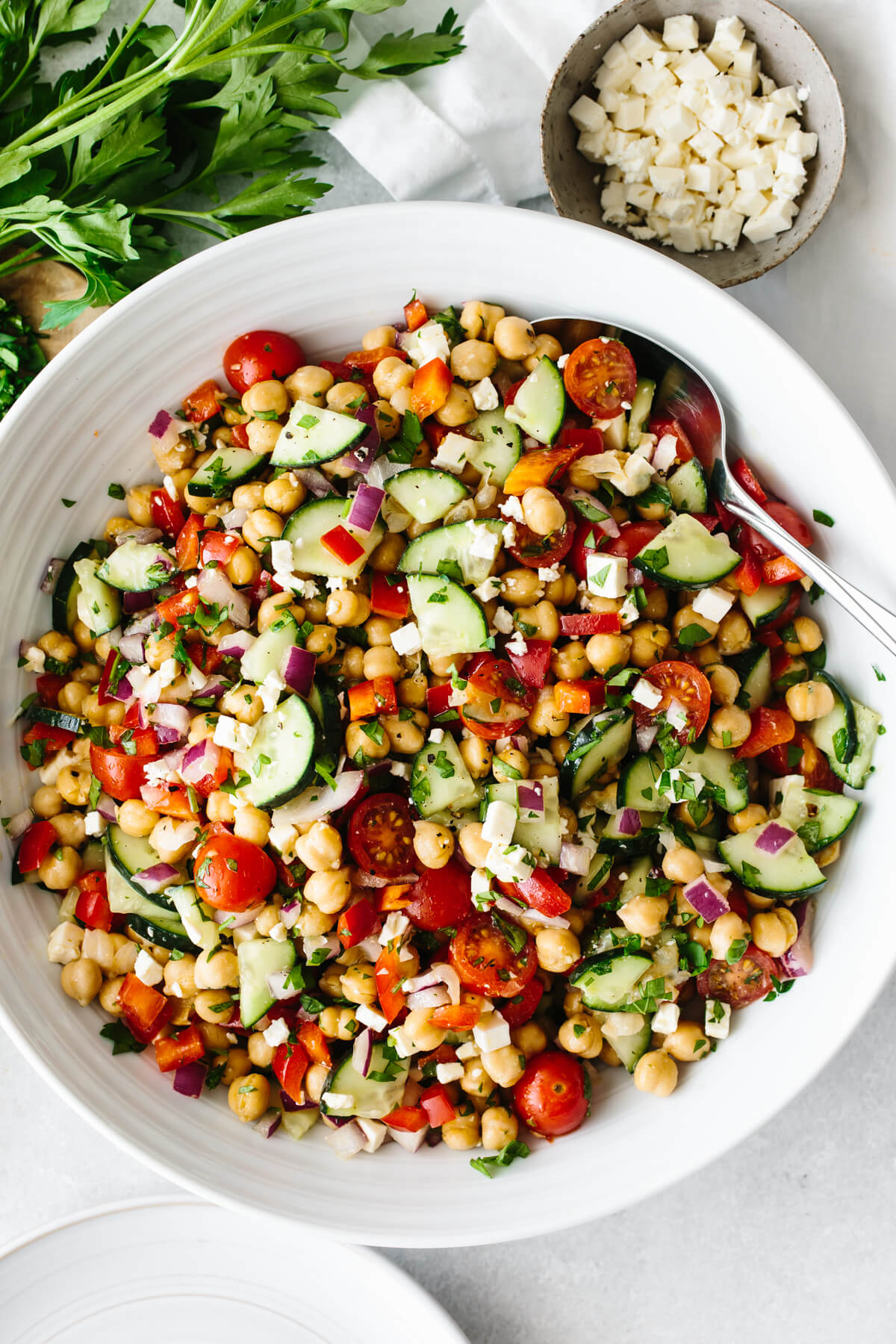 Mediterranean chickpea salad in a large white bowl on a table.