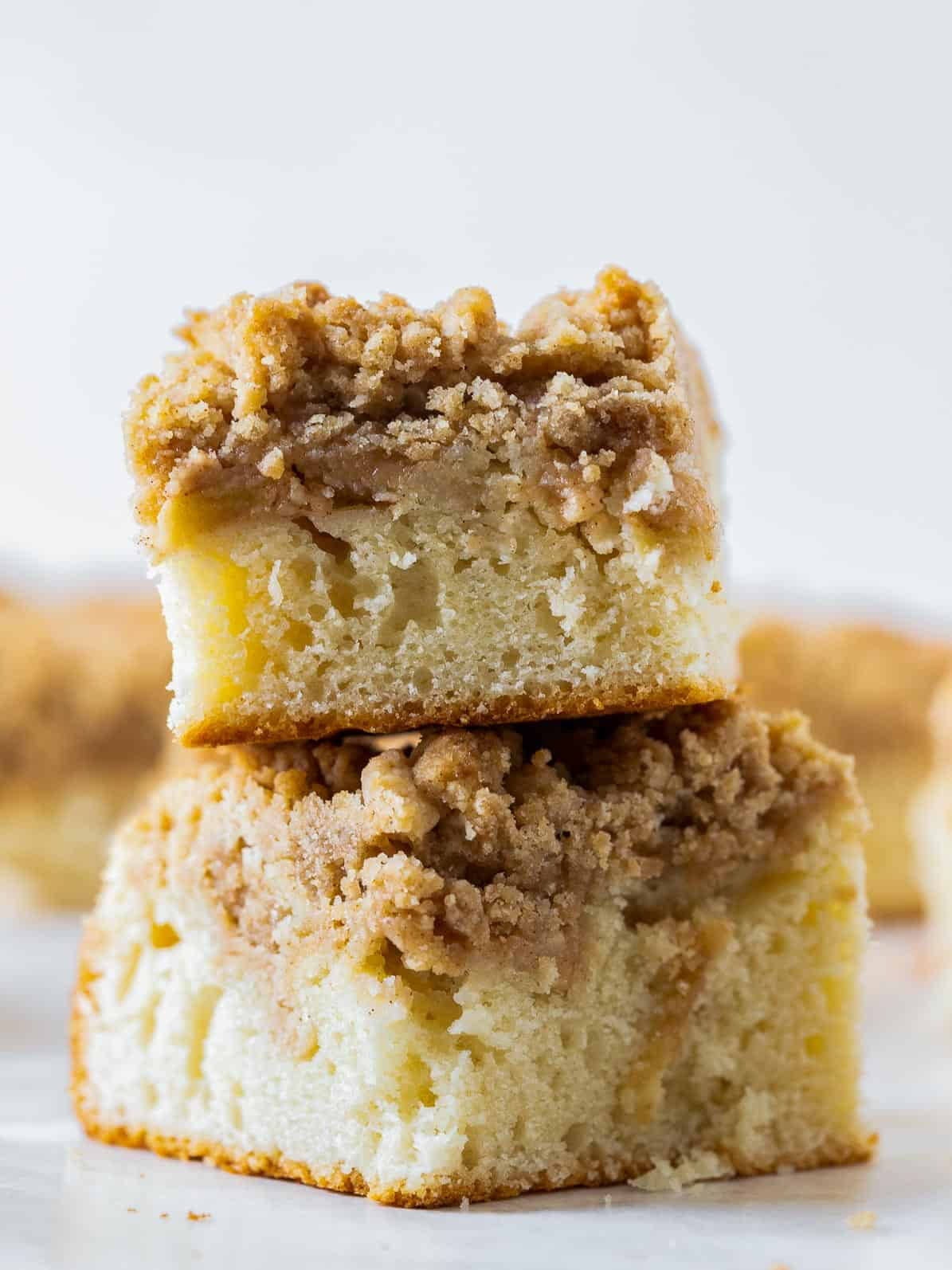 two apple crumb cake pieces stacked on top of each other.