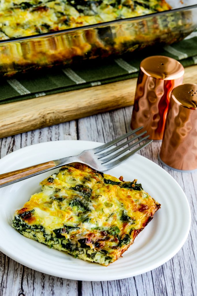 one piece of Kale, Mozzarella, and Egg Bake on plate with casserole dish in background