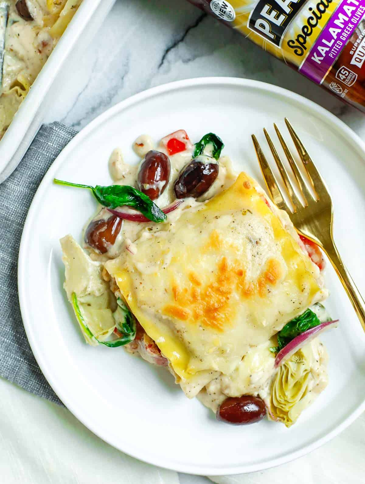 Piece of Greek White Alfredo Lasagna Roll on a plate with a gold fork